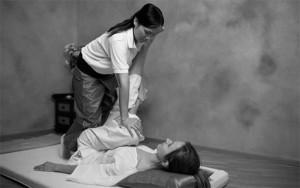 Mulher fazendo massagem tailandesa em cliente